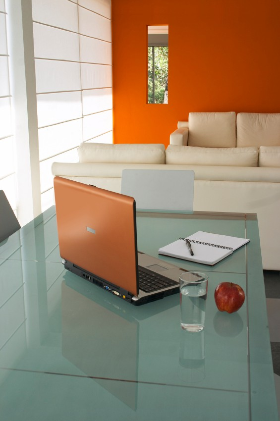 Modern minimalistic interior, with sofas, glass table, and steel chairs and orange wall. Orange laptop, notebook, apple and glass of water over the glass table suggest working at home.